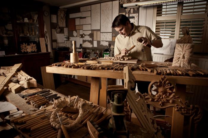 Муж вырезает посуду на деревянную свадьбу