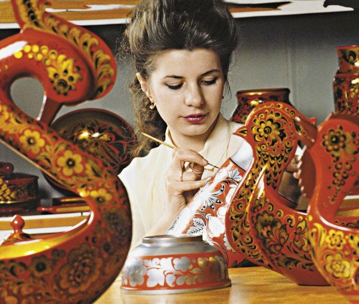 Жена расписывает посуду на деревянную свадьбу